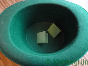 Wahl zum Kistengrün 2016:Zwei grüne, gefaltete Papiere in einem grünen Hut