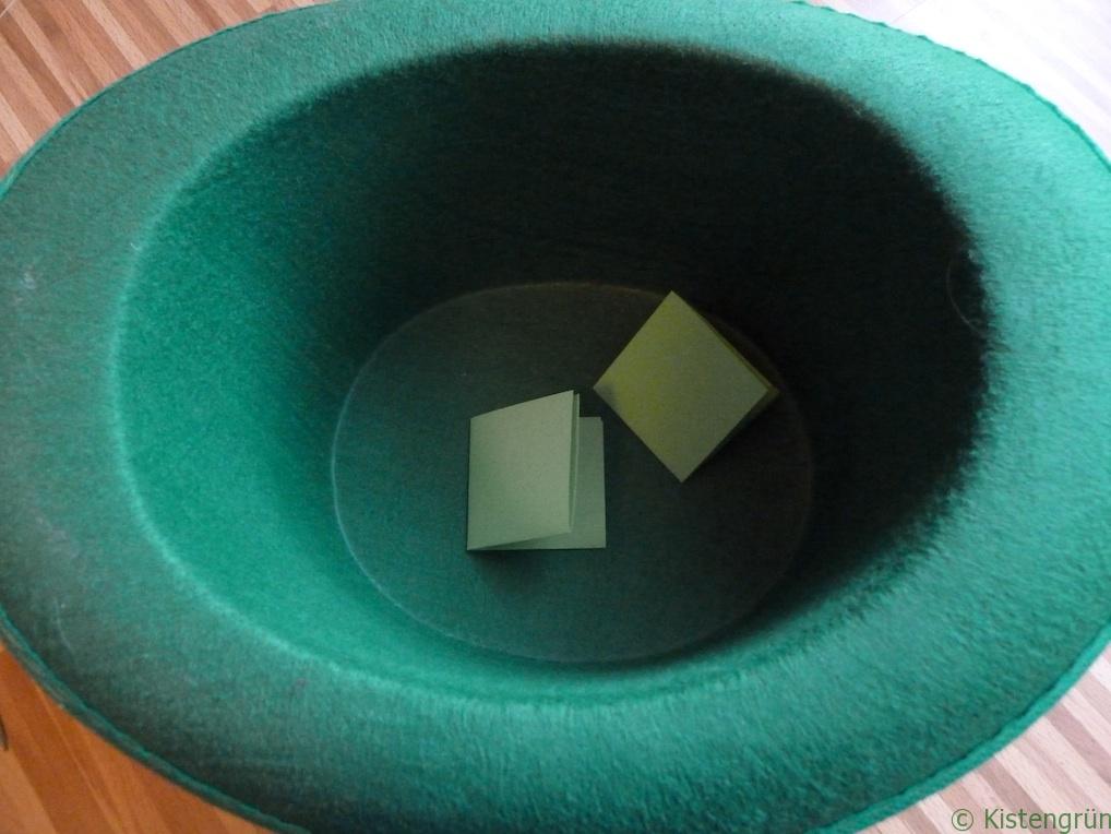 Wahl zum Kistengrün 2016: Zwei grüne, gefaltete Papiere in einem grünen Hut