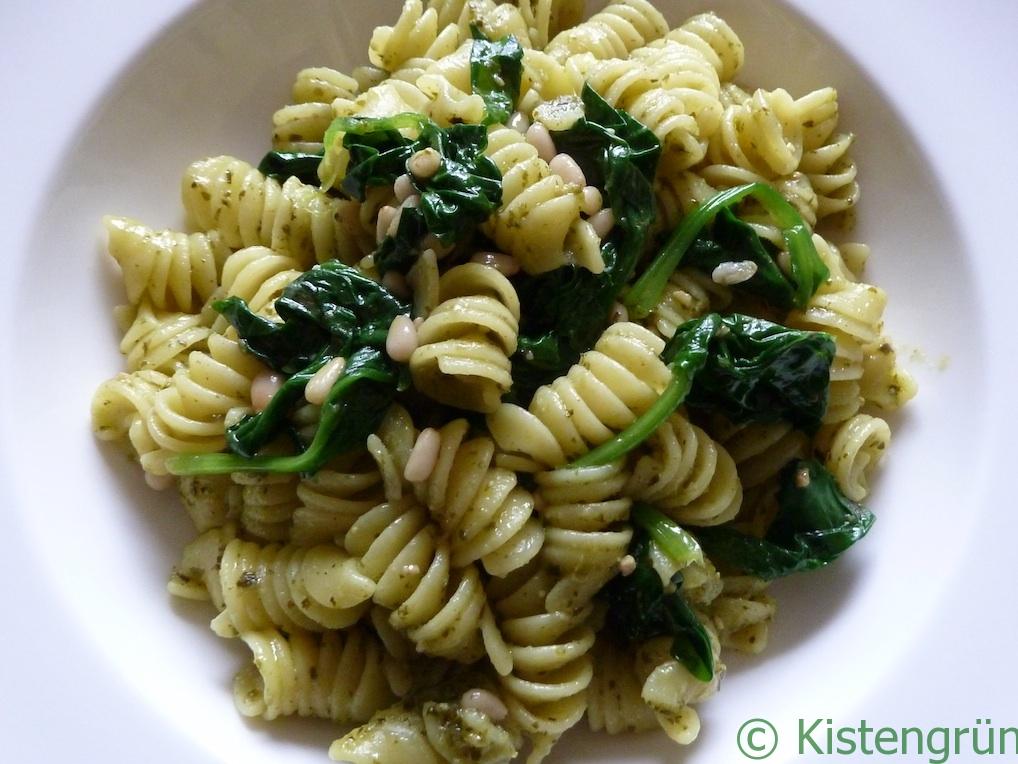 Pesto-Pasta mit blanchiertem Spinat und Pinienkernen in einem weißen Teller