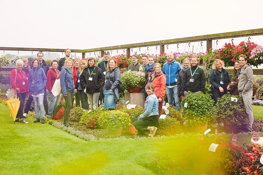 Gartenbloggertreffen: Gartenblogger stehen in einem Blumenbeet bei Volmary