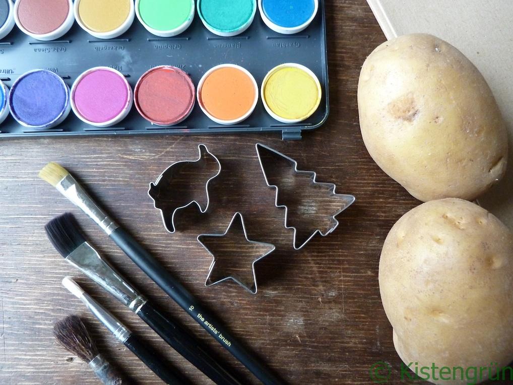 Auf einem Holztische liegen zwei Kartoffeln, vier Pinsel, ein Tuschkasten, ein Boden Packpapier und drei weihnahcteliche Keksausstecher