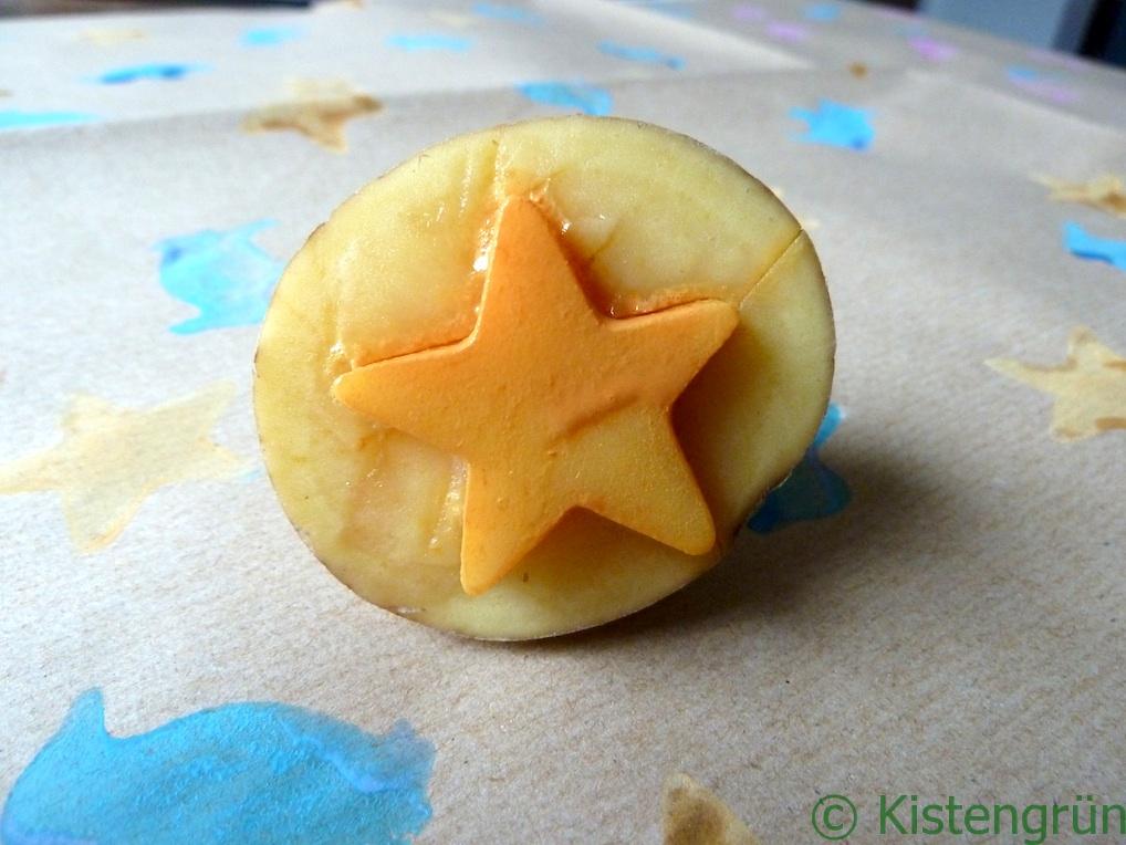 Eine Kartoffelstempel mit einem orangenen Stern auf einem Bogen selbst gestaltetem Geschenkpapier
