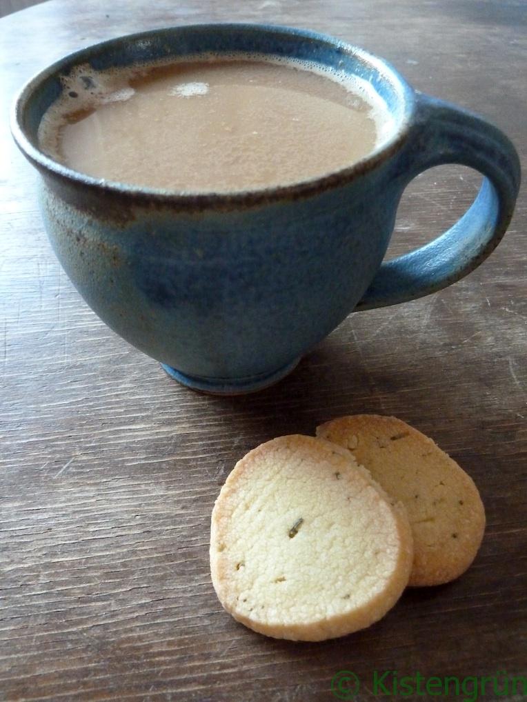 Eine blaue Tontasse mit Milchkaffee und zwei Rosmarin-Kekse