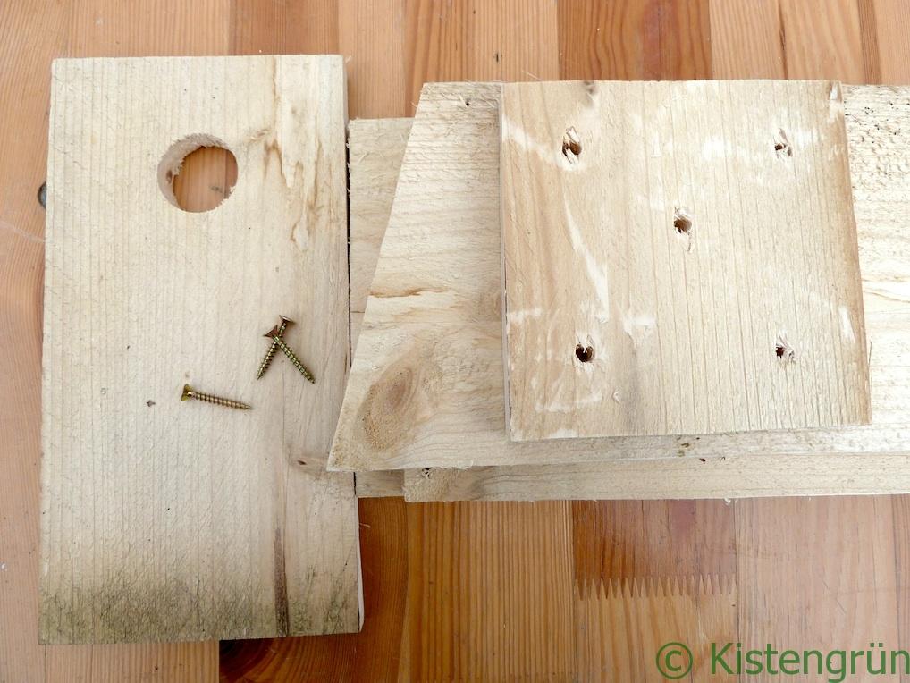 Bausatz für einen Nistkasten: eine paar Bretter und Schrauben auf einem Holztisch.