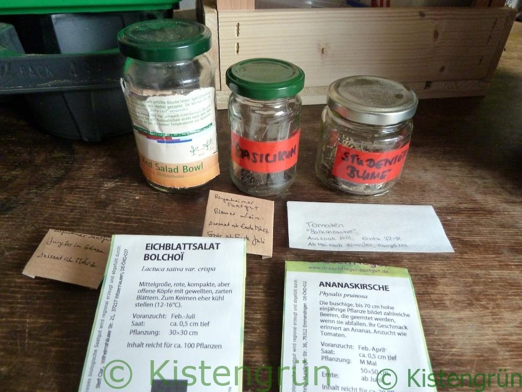 Tüten und Einmachgläser mit verschiedenen Samenkörnern, unter anderem Salat, Studentenblume und Basilikum