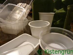 diverse Plastikschalen und Plastikbecher auf einem brauen Tisch