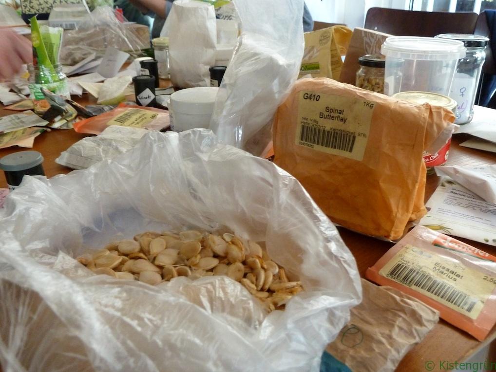 Verschiedene Tüten mit Pflanzensamen liegen bei einer Saatgut-Börse auf einem Tisch.