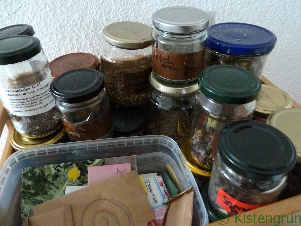Eine Holzkisten mit Gläsern, die mit verschiedenem Pflanzensamen gefüllt sind.