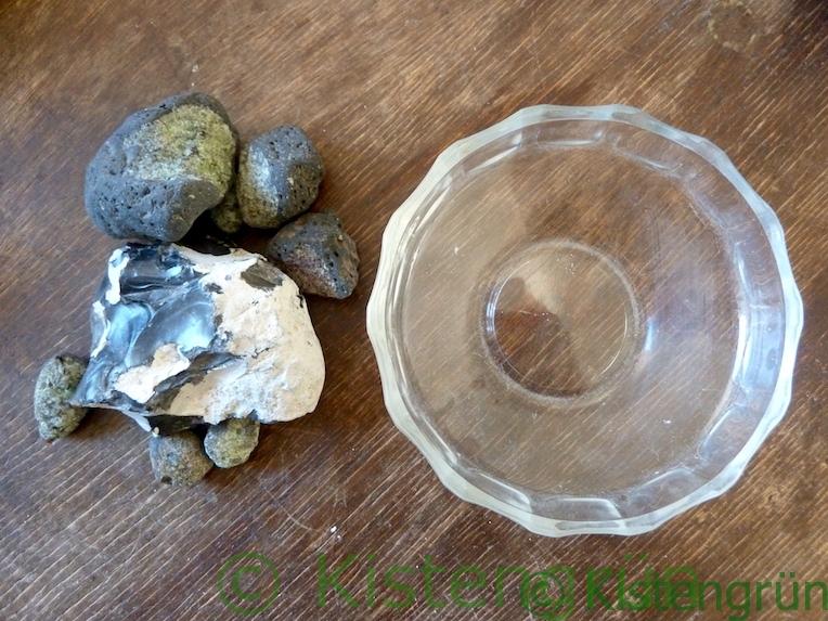 Steine und eine flache Schale für eine Bienentränke