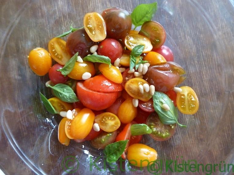 einfacher Tomatensalat mit Basilikum und Pinienkernen in einer Glasschüssel