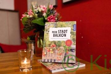 Das Buch Mein Stadtbalkon steht auf einem Tisch mit einem Blumenstrauß