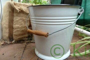 Wasser sammeln: weißer Emaille-Eimer auf dem Balkon